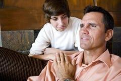 Père avec le fils adolescent à la maison sur le sofa image stock