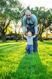 Père avec le fils de bébé dans le voisinage vert Images stock