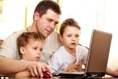 Père avec ses enfants à l'aide de l'ordinateur portatif photos stock