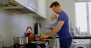 Père avec son bébé garçon préparant la nourriture dans la cuisine 4k banque de vidéos