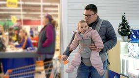 Père avec son enfant dans le transporteur de bébé dans le centre commercial, concept de parenting d'attachement banque de vidéos