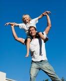 Père avec son fils sur le sien en arrière Images stock