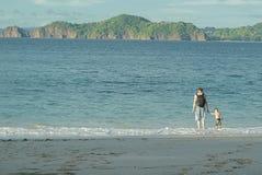 Père avec un sac à dos tenant la main de son fils par la mer Ils entrent dans l'eau contre le contexte de belles îles photos stock