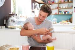 Père With Baby Daughter vérifiant le téléphone portable dans la cuisine Photographie stock