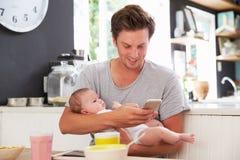 Père With Baby Daughter vérifiant le téléphone portable dans la cuisine Photos libres de droits