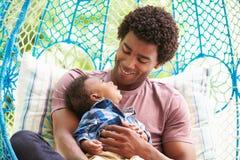 Père With Baby Son détendant sur l'oscillation extérieure Seat de jardin Image libre de droits
