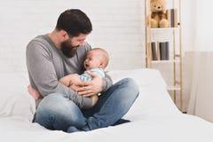 Père barbu essayant de calmer vers le bas le bébé nouveau-né images stock