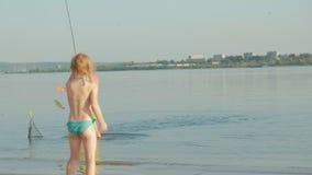 Père beau affectueux et fille adorable avec les cannes à pêche appréciant la pêche ensemble tout en se tenant dans l'eau clips vidéos