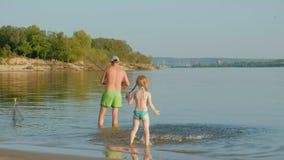 Père beau affectueux et fille adorable avec les cannes à pêche appréciant la pêche ensemble tout en se tenant dans l'eau banque de vidéos