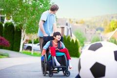 Père caucasien aidant le fils biracial handicapé dans le pla de fauteuil roulant Image libre de droits
