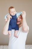Père caucasien dans le T-shirt blanc, tenant le fils nouveau-né de bébé sur des épaules Photographie stock libre de droits