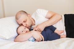 père caucasien de Moyen Âge dans le T-shirt blanc se situant dans le lit avec le fils nouveau-né de bébé Photo stock