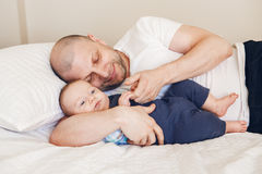 père caucasien de Moyen Âge dans le T-shirt blanc se situant dans le lit avec le fils nouveau-né de bébé Photographie stock