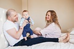 Père caucasien et mère de famille s'asseyant sur le lit dans la chambre à coucher, tenant prendre le fils nouveau-né de bébé Photo libre de droits