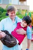 Père caucasien portant le fils handicapé biracial sur le terrain de jeu Images stock