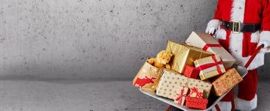 Père Christmas avec une brouette complètement des cadeaux enveloppés colorés de Noël dans une bannière de panorama au-dessus de m images stock