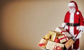 Père Christmas livrant une brouette des cadeaux enveloppés colorés au-dessus d'un fond brun de gradient avec l'espace de copie images stock