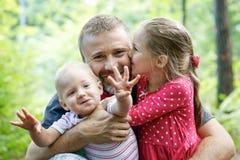 Père consacré étreignant son fils et fille, appréciant l'extérieur images stock