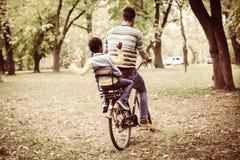 Père d'afro-américain conduisant sa petite fille sur le trou de vélo Photos stock