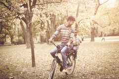 Père d'afro-américain conduisant sa petite fille sur le vélo Photos stock