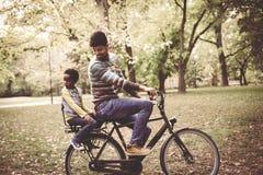 Père d'afro-américain conduisant sa petite fille sur le vélo t Image stock