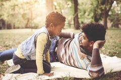 Père d'afro-américain se situant dans le pré avec la fille Images libres de droits