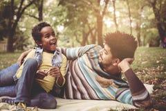 Père d'afro-américain se situant dans le pré avec la fille et Photographie stock