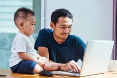 Père d'homme travaillant sur l'ordinateur portable photos libres de droits