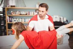 Père dans le costume de super héros tout en portant la fille Image libre de droits