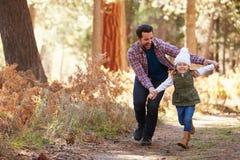 Père And Daughter Running par la région boisée d'automne photos libres de droits