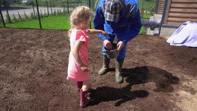 Père de aide de fille avec l'herbe de pelouse semant la truie dans la cour de maison urbaine Tenu dans la main banque de vidéos