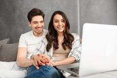 Père de famille heureux et femme s'asseyant ensemble sur le divan d'intérieur, et Photo stock