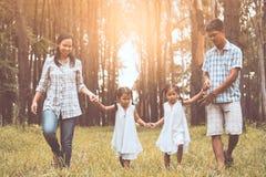 Père de famille, mère et deux filles de petit enfant tenant la main Image libre de droits