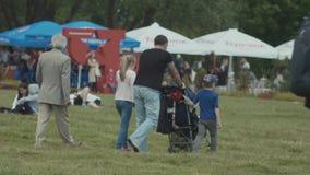 Père de famille poussant la voiture d'enfant marchant avec des enfants sur la pelouse en parc de ville banque de vidéos