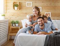 Père de mère de famille et enfants heureux fille et fils dans le lit Images stock