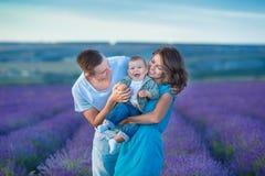Père de mère de portrait de famille et fils de bébé sur le gisement de lavande ayant l'amusement ensemble Ajouter heureux à l'enf photo stock