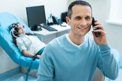 Père de petit patient parlant au téléphone Images stock