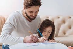 Père de soin agréable aidant sa fille Photos stock