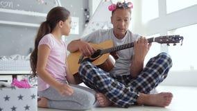 Père de soin agréable jouant la guitare à la maison banque de vidéos