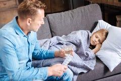 Père de soin apportant la médecine à son fils malade Photos stock