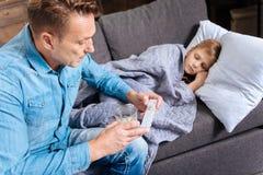 Père de soin donnant des pilules à son fils malade Photo libre de droits