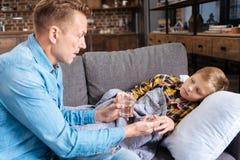 Père de soin donnant la médecine à son fils malade Photographie stock libre de droits
