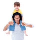 Père de soin donnant sur le dos la conduite à son garçon photo stock