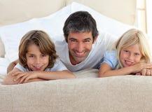 Père de soin et ses enfants se trouvant sur un bâti images stock