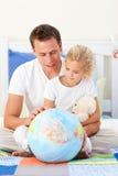 Père de soin et son descendant regardant un globe photo libre de droits