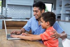 Père de sourire à l'aide de l'ordinateur portable avec son fils Photo libre de droits