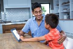 Père de sourire à l'aide du comprimé avec son fils photographie stock libre de droits