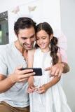 Père de sourire à l'aide du smartphone avec la fille Image libre de droits
