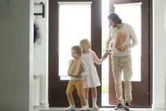 Père de sourire avec des enfants revenant à la maison tenant des sacs en papier Photos stock