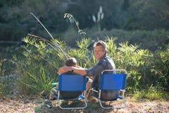 Père de sourire avec la pêche de fils le jour ensoleillé Photographie stock